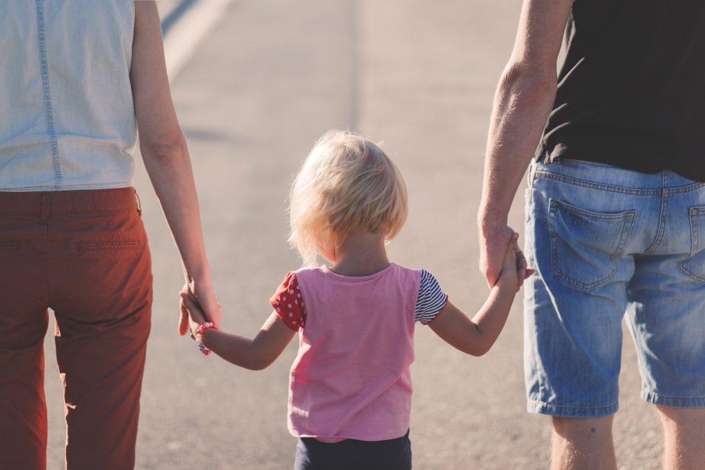 Familjerätt, föräldrar håller sitt barn i handen