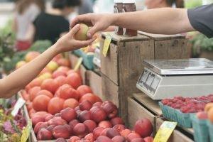 Avtal, bilden föreställer en person som handlar frukt på en marknad