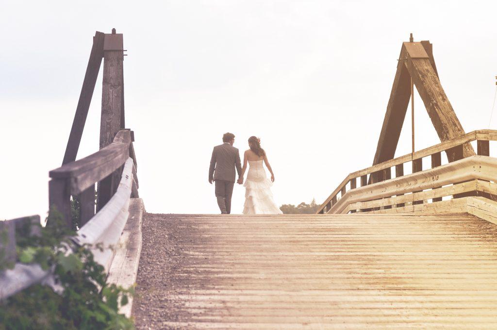 Äktenskap, nygift par som går på en bro samt håller varandra i handen.