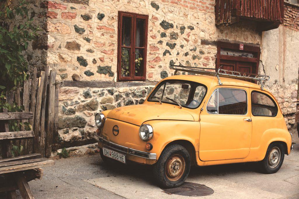 Begagnade varor. En gul bil som står parkerad vid ett hus.