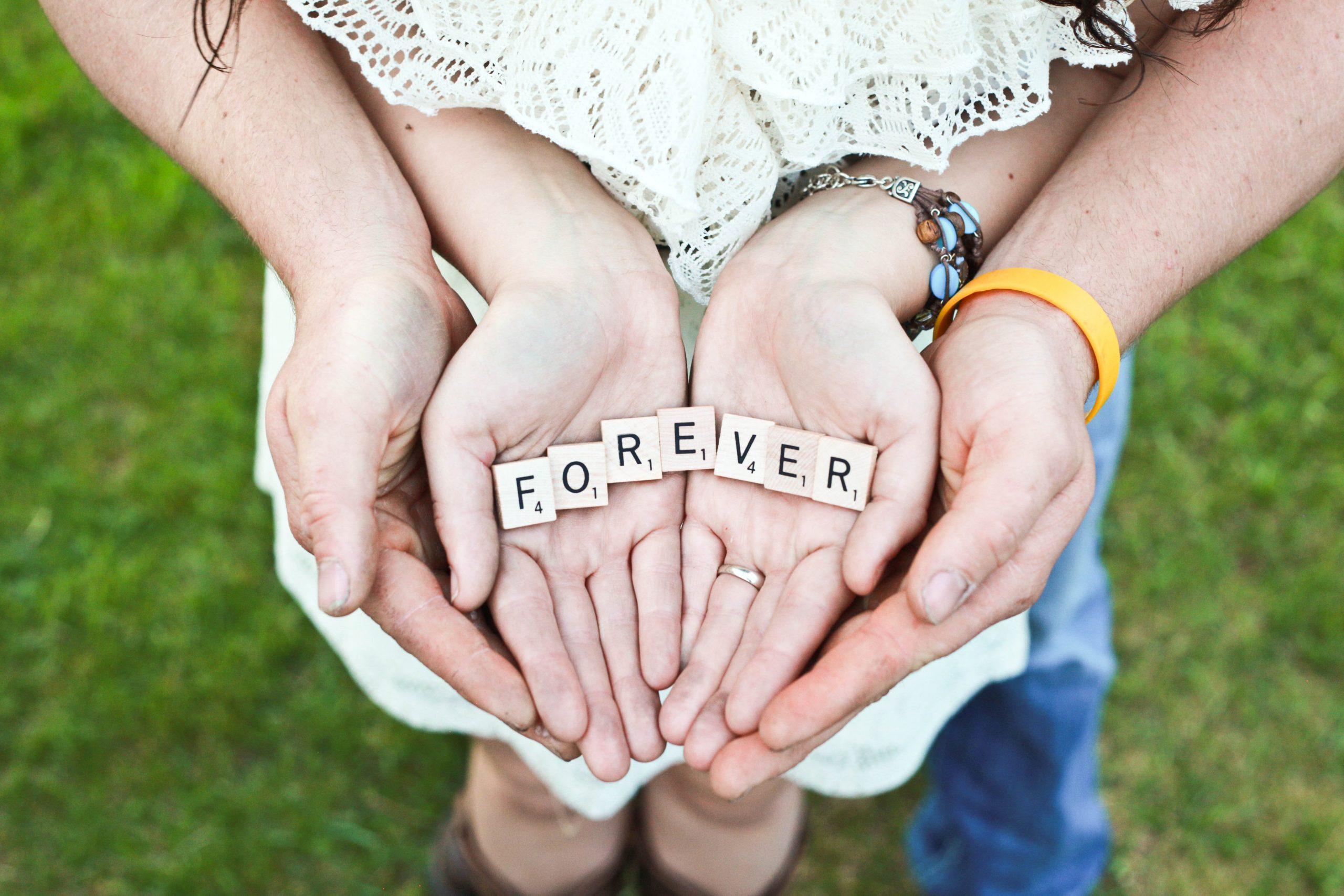 """Händer som hålls samman med ordbrickor där det står """"forever"""""""